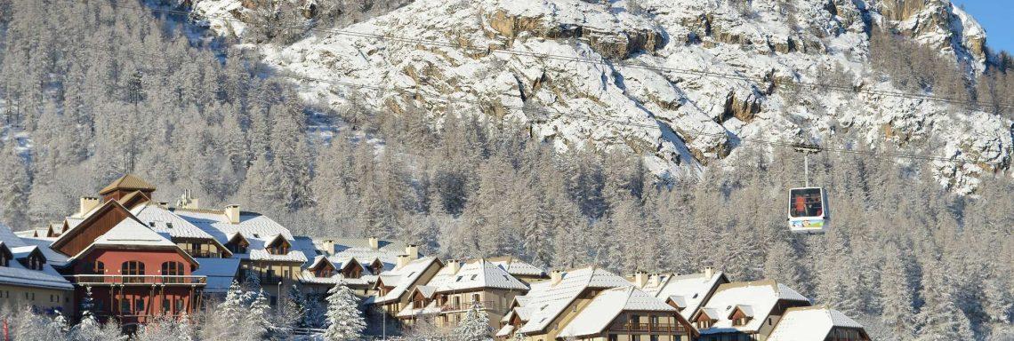 Club Med Serre-Chevalier, en France - Vue extérieure enneigée du Club Med à flan de montagne