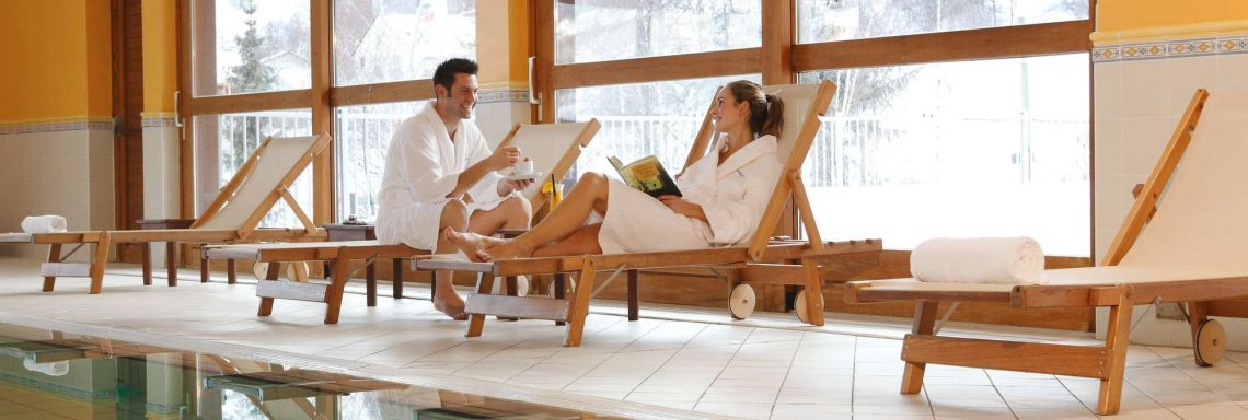 Club Med Serre-Chevalier, en France - Image d'un couple au bord de la piscine intérieure avec vue sur la montagne enneigée