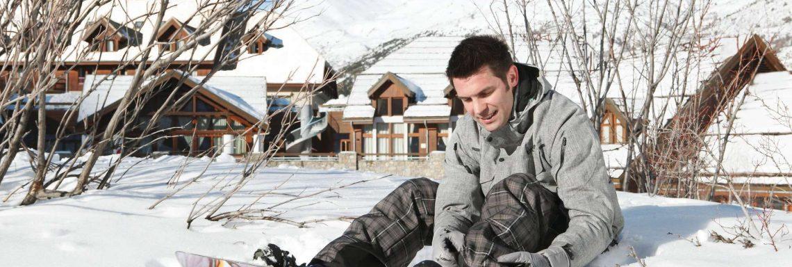 Club Med Serre-Chevalier, en France - Image d'un homme assis dans la neige avec une planche de snowboard