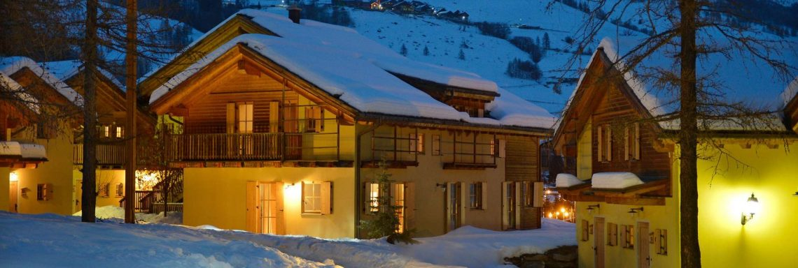 Club Med Pragelato Vialattea, en Italie - Petits chalets deux étages éclairés, en soirée.