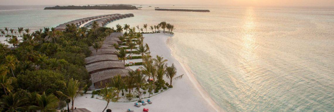 Club Med Villas de FInolhu, aux Maldives - Vue aérienne de la plage avec les villas devant la lagune au coucher du soleil