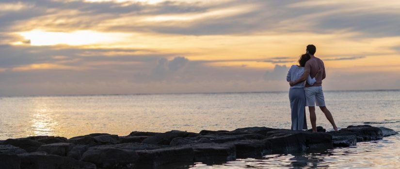 Couple sur une jetée regardant un coucher de soleil