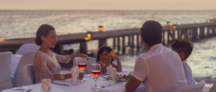 Club Med Kani, aux Maldives - Une famille profitant d'un repas en soirée, sur une terrasse extérieure.