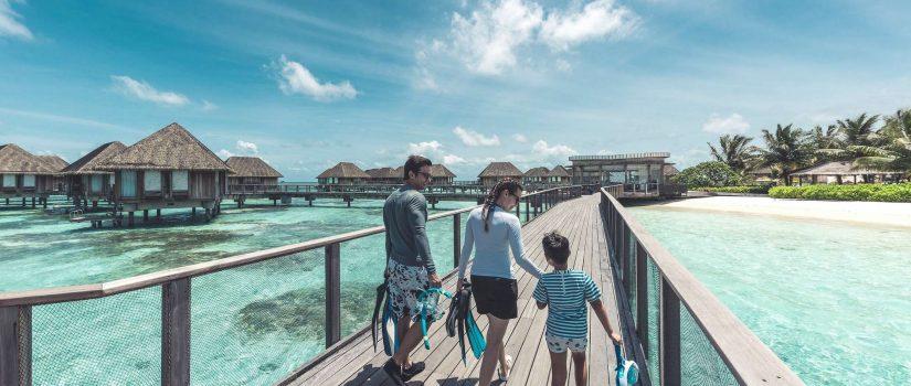 Club Med Kani, aux Maldives - Une famille marche sur un pont de bois, surplombant l'Océan.
