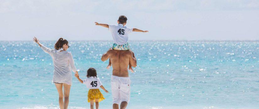 Club Med Kani, aux Maldives - Une famille de quatre personnes profitant de la plage en journée.