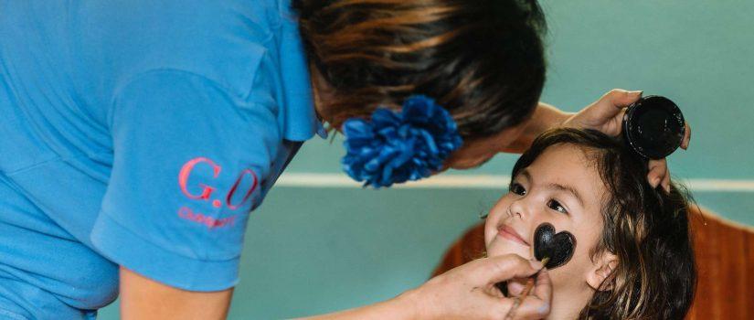 Club Med Kani, aux Maldives - Une petite fille se fait peinturer le visage par une maquilleuse.