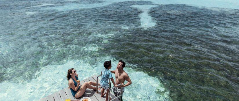 Club Med Kani, aux Maldives - Une famille mange et ris sur le bord d'un ponton.