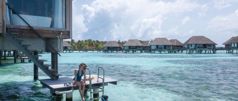 Club Med Kani, aux Maldives - Un couple est sur leur balcon extérieure et se baigne dans l'Océan.