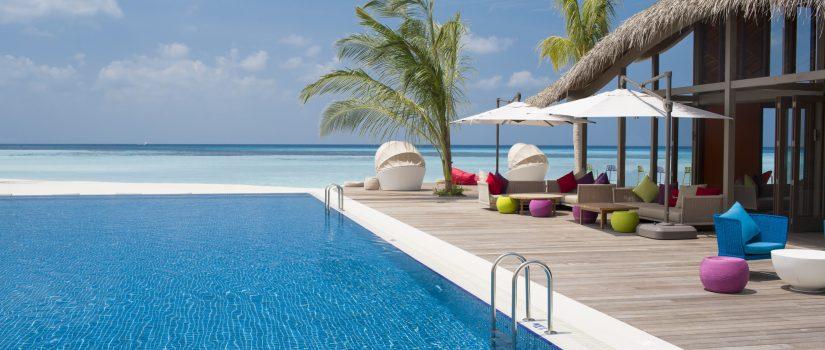 Club Med Kani, aux Maldives - Vue en biais de la seule piscine extérieure avec palmiers et chaises longues.