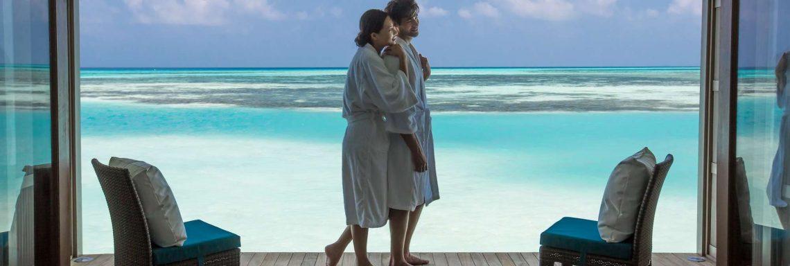 Club Med Villas de FInolhu, aux Maldives - Photo d'un couple sur la terrasse d'une villa devant la lagune bleu turquoise
