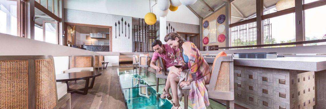 Club Med Villas de FInolhu, aux Maldives - Vue intérieure du restaurant où deux personnes regardent le sol vitré avec vue sous marine