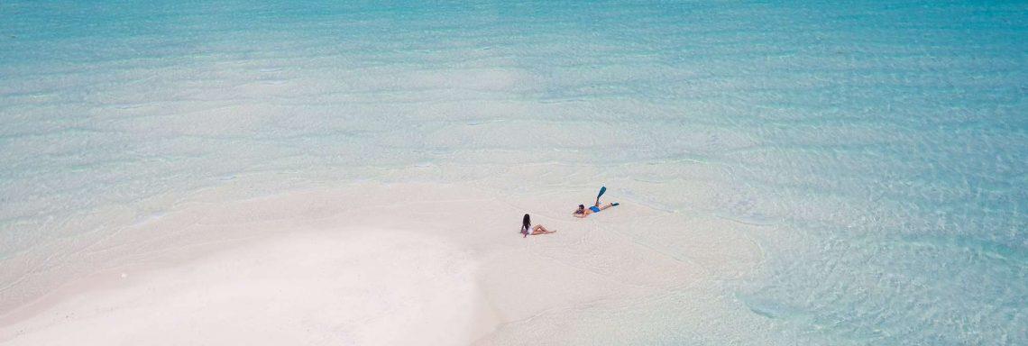 Club Med Villas de FInolhu, aux Maldives - Photo aérienne de deux personnes, seules sur la plage de la lagune