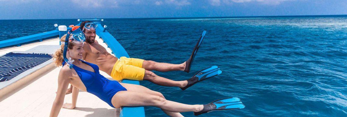 Club Med Villas de FInolhu, aux Maldives - Photo d'un couple sur un bateau s'apprêtant à plonger avec masques et tuba