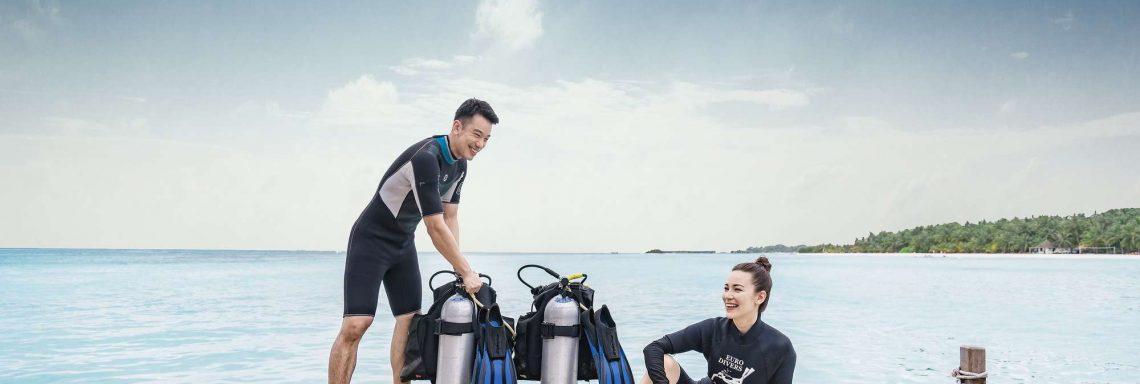 Club Med Villas de FInolhu, aux Maldives - Photo de deux personnes souriantes s'apprêtant à plonger devant l'océan avec bonbonnes