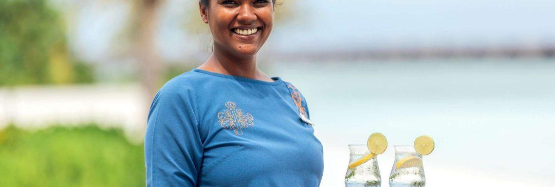 Club Med Villas de FInolhu, aux Maldives - Photo d'une employée du Club Med servant des cocktail sur la plage