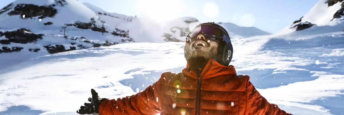 Photo d'un homme souriant dans un paysage de montagne enneigée