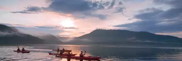 Photo d'un groupe de personne faisant du kayak sur un lac au coucher du soleil