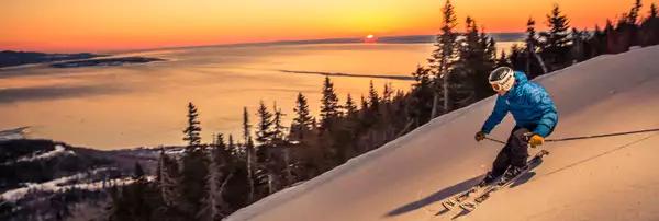 Photo d'un skieur descendant une piste de ski devant un coucher de soleil