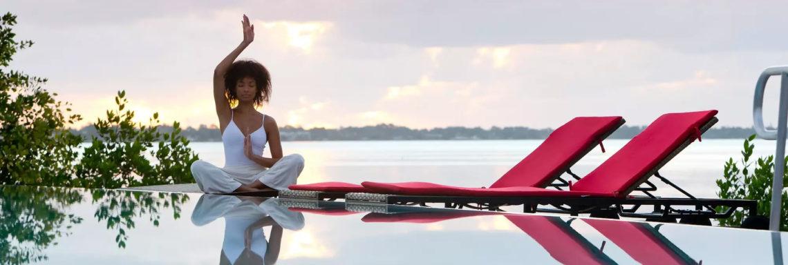 Club Med Sandpiper Bay, Floride - une femme fait du yoga en mâtiné, sur le bord de la piscine