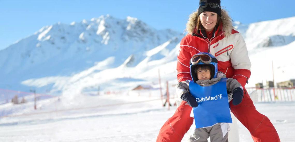 Club Med La Plagne 2100, France - Une G.O aide un jeune enfant à faire ses débuts en ski